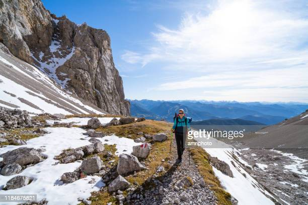 happy 45 years old woman hiking alone in mountains with first snow - 45 49 anni foto e immagini stock