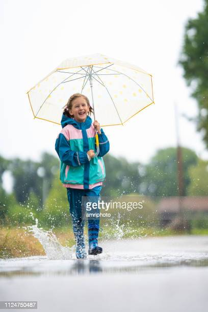 happy 6 years old girl in rain clothes and umbrella walking through puddle - 6 7 years stock pictures, royalty-free photos & images