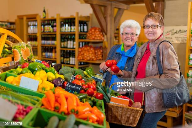 happy 65 to 70 years old senior women shopping in grocery - 65 69 years stock pictures, royalty-free photos & images