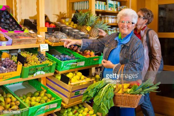 Gelukkig 70 jaar oude vrouw in supermarkt glimlachend op camera