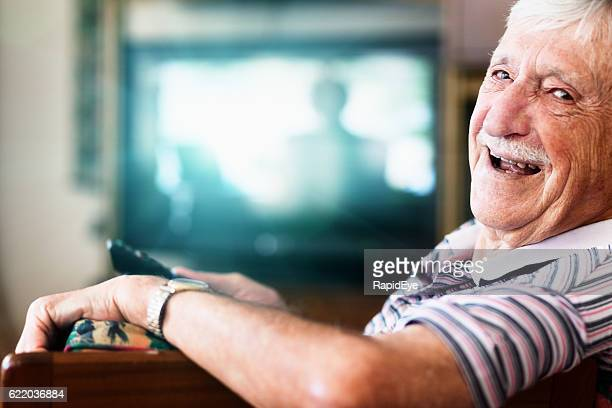 happy 90-year-old man in charge of the tv remote control - watch what happens: live stock-fotos und bilder