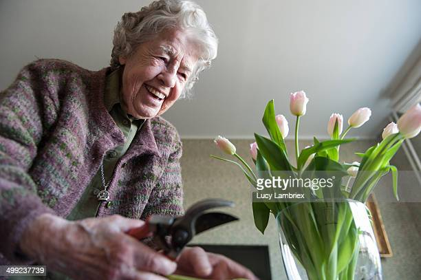 Happy 97-year-old lady putting tulips in vase