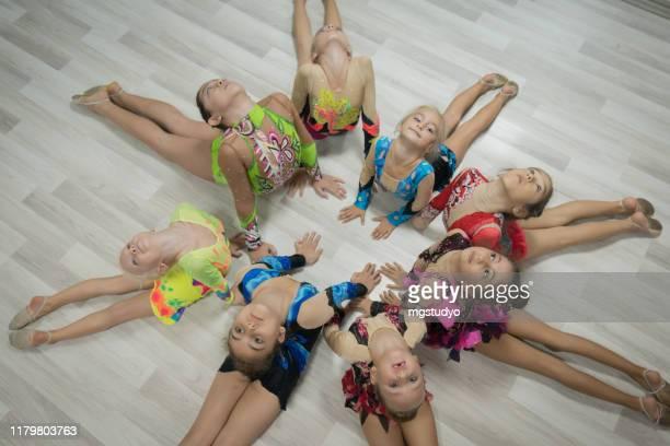 danseurs acrobatiques heureux se trouvant sur le plancher. - gymnastique au sol photos et images de collection