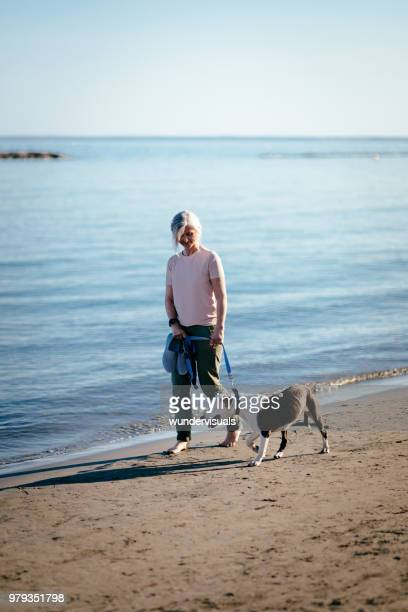 Happy active retired woman walking with pet dog on beach