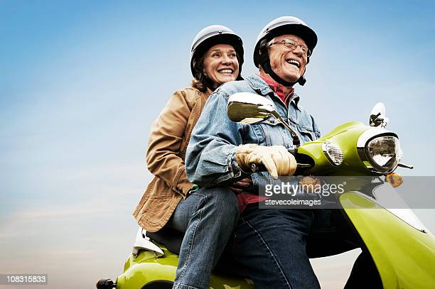 happy active senior couple on scooter - actieve ouderen stockfoto's en -beelden