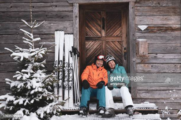 happy active senior couple on ski holidays - ski holiday stock pictures, royalty-free photos & images