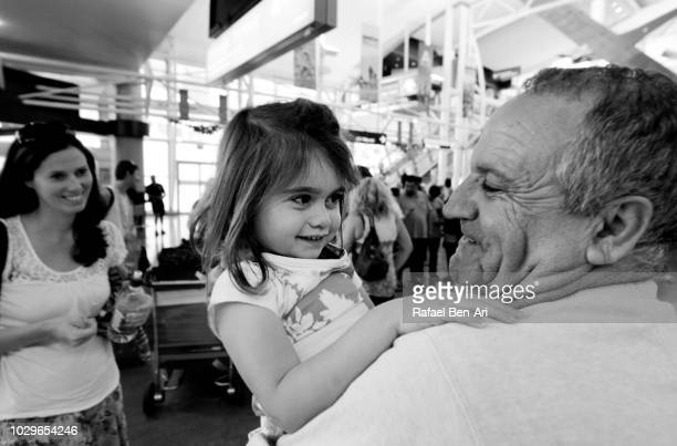 happy active senior grandfather holding his granddaughter - rafael ben ari stock pictures, royalty-free photos & images