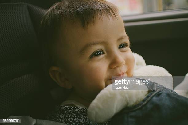 Happy adorable baby girl in car