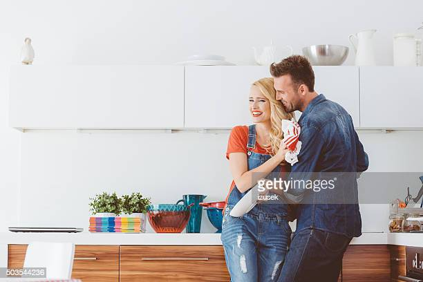 Happy adult couple cleaning dishes in the kitchen