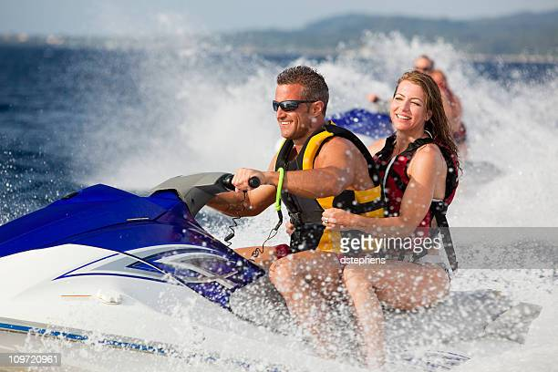Happy adult couple enjoying ride on jetski