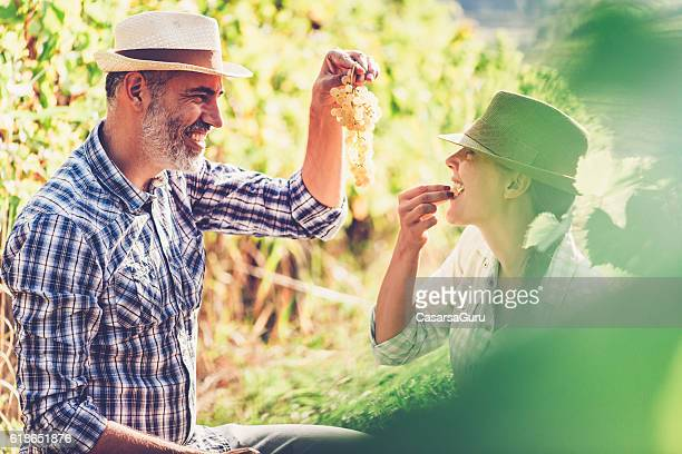 Happy adult Couple in the Vineyard during the Harvest
