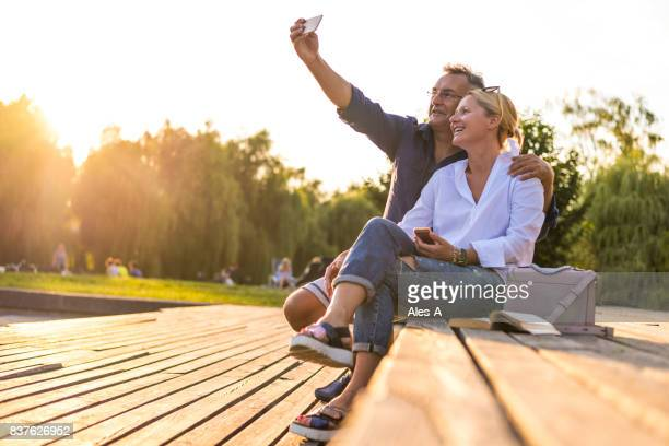 happy adult couple taking selfie in a park - heterosexual couple imagens e fotografias de stock