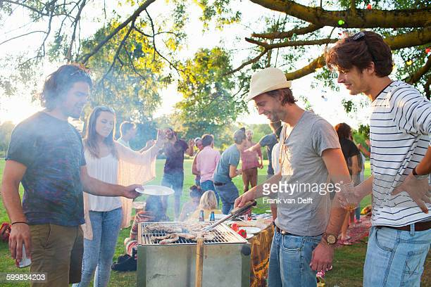 Happy adult friends barbecuing at sunset party in park