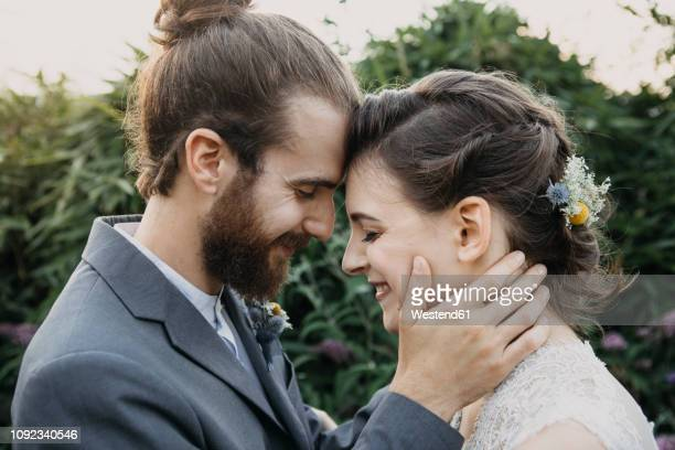 happy affectionate bride and groom outdoors - heterosexual couple photos - fotografias e filmes do acervo