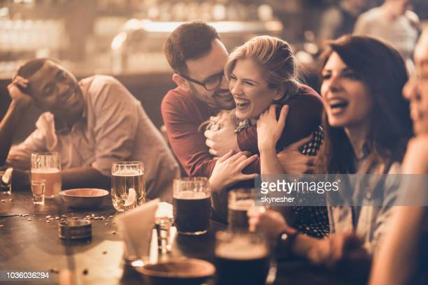 happy affectionate couple having fun with their friends in a pub. - medium group of people stock pictures, royalty-free photos & images