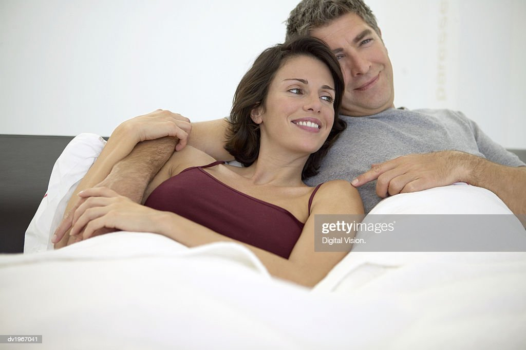 Happy, Affectionate Couple Lie Side by Side in Bed : Stock Photo