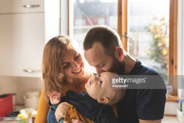 happy affectionate family in the kitchen at home - real life stock pictures, royalty-free photos & images