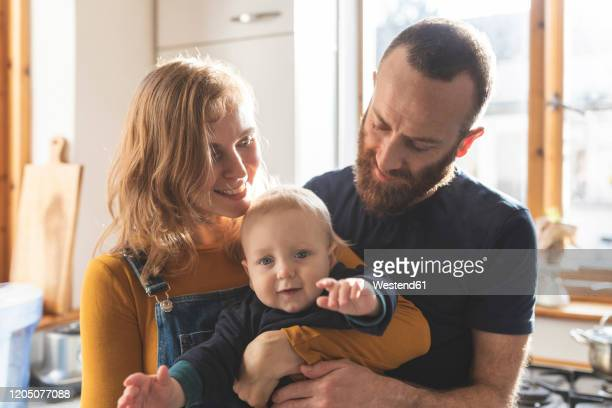 happy affectionate family in the kitchen at home - baby stock pictures, royalty-free photos & images