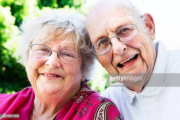 Happy, affectionate old couple smile at camera