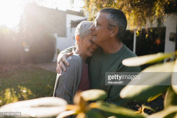 happy affectionate senior couple hugging in garden - wife stock pictures, royalty-free photos & images