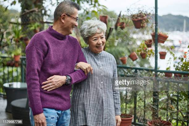 happy affectionate senior couple walking together - east asian ethnicity stock pictures, royalty-free photos & images