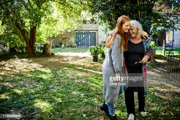 happy affectionate senior woman and young woman in garden - copy space stock pictures, royalty-free photos & images