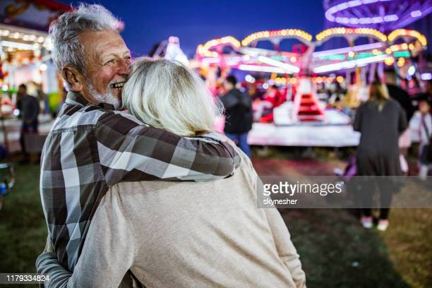 séniores afectuosos felizes que apreciam no parque de diversões em noite - vida real - fotografias e filmes do acervo