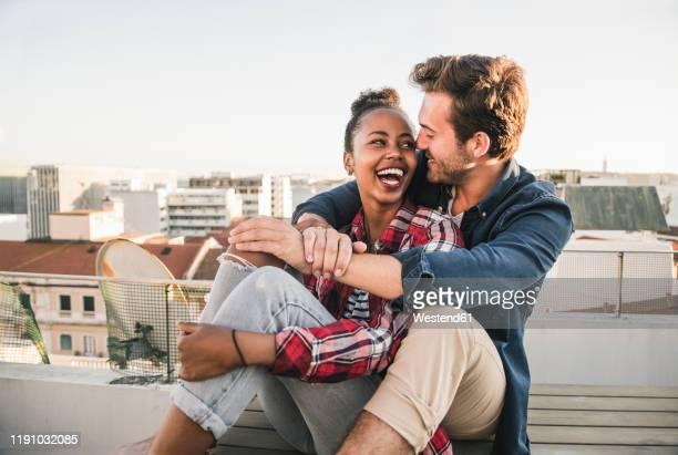 happy affectionate young couple sitting on rooftop in the evening - freundschaftliche verbundenheit stock-fotos und bilder