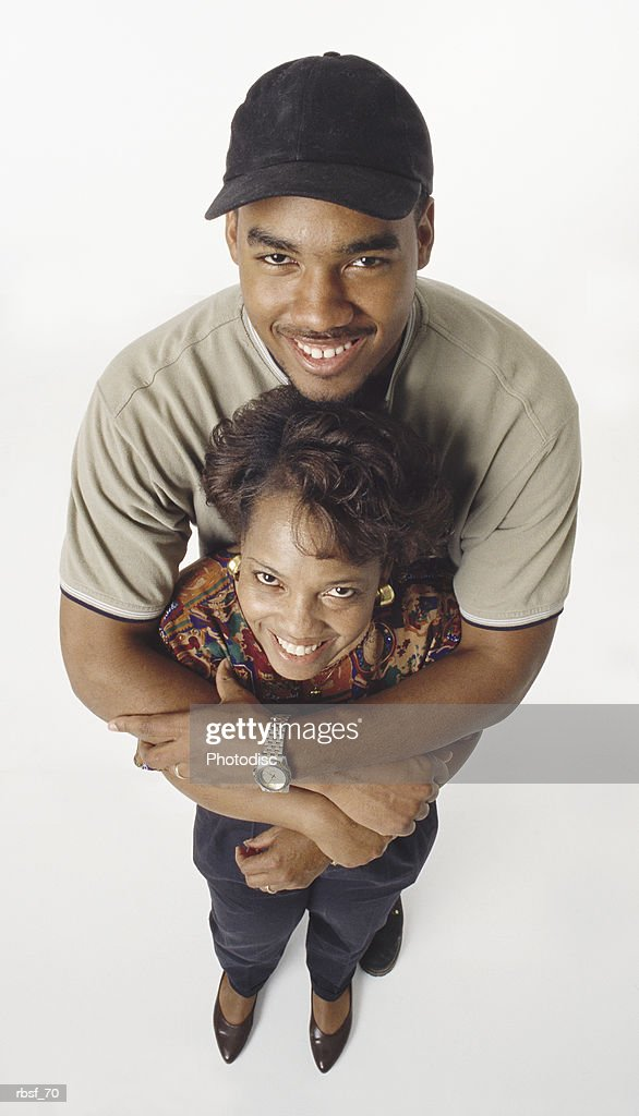 happy african american adult son stands behind and holds mom : Foto de stock