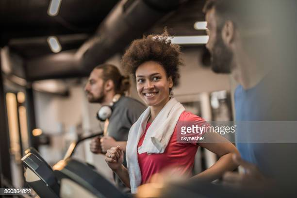 Happy African American athletic woman running in a gym and talking to man next to her.