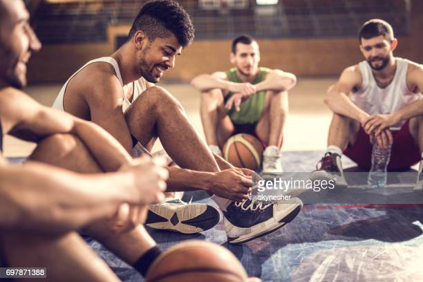Happy African American basketball player tying shoelace while relaxing on basketball court with friends.