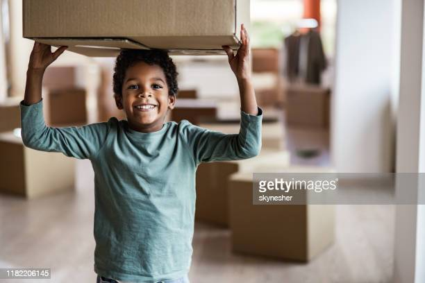 happy african american boy carrying carton box on his head at new home. - children only stock pictures, royalty-free photos & images
