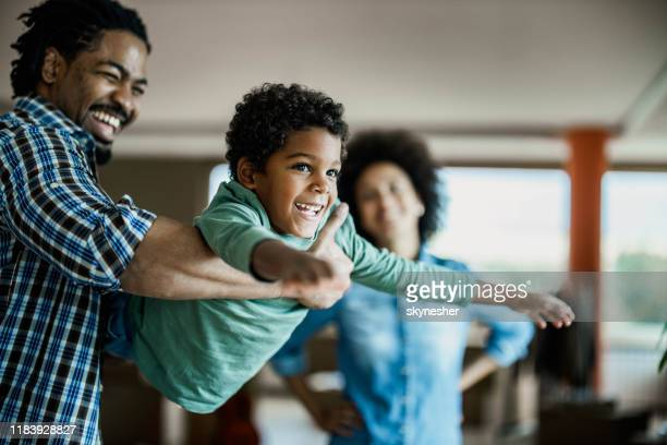 happy african american boy having fun with his father at home. - espontânea imagens e fotografias de stock