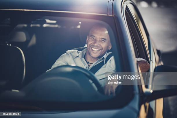 happy african american businessman going on a trip by car. - driver stock pictures, royalty-free photos & images