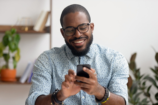 Happy african american businessman using phone mobile apps at workplace 1150384559