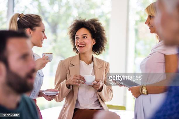happy african american businesswoman talking to her colleagues on a coffee break at casual office. - coffee break stock pictures, royalty-free photos & images