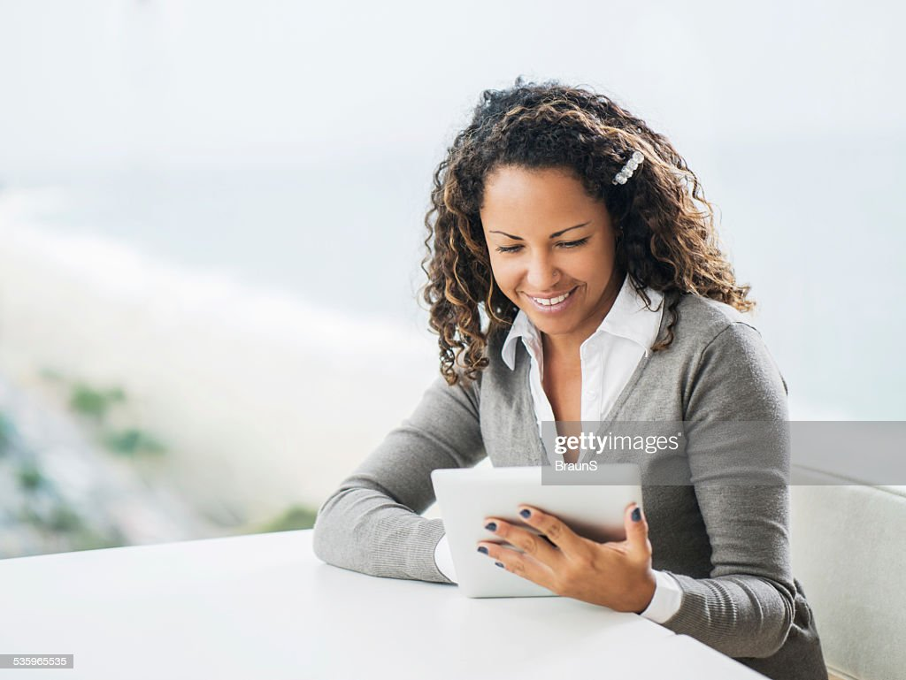 Happy African American businesswoman using touchpad. : Stock Photo