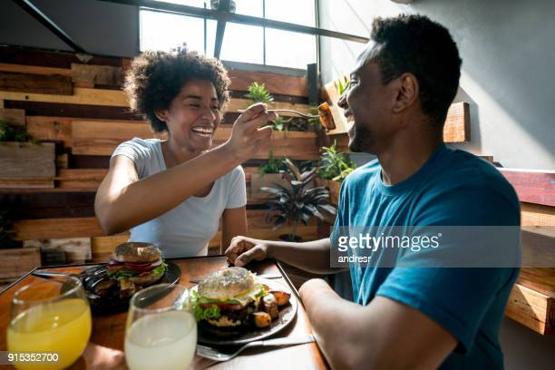 Happy african american couple at a restaurant and woman feeding her boyfriend