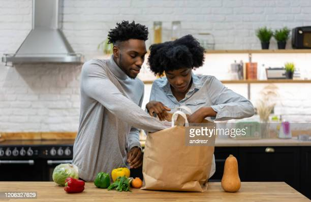 happy african american couple at home unpacking the groceries - unpacking stock pictures, royalty-free photos & images