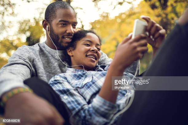 Gelukkige African American paar genieten van goede muziek tijdens herfstdag in de natuur.