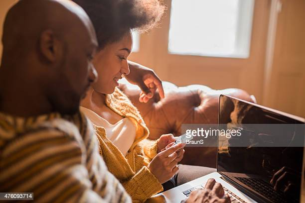 Happy African American couple enjoying in home shopping together.