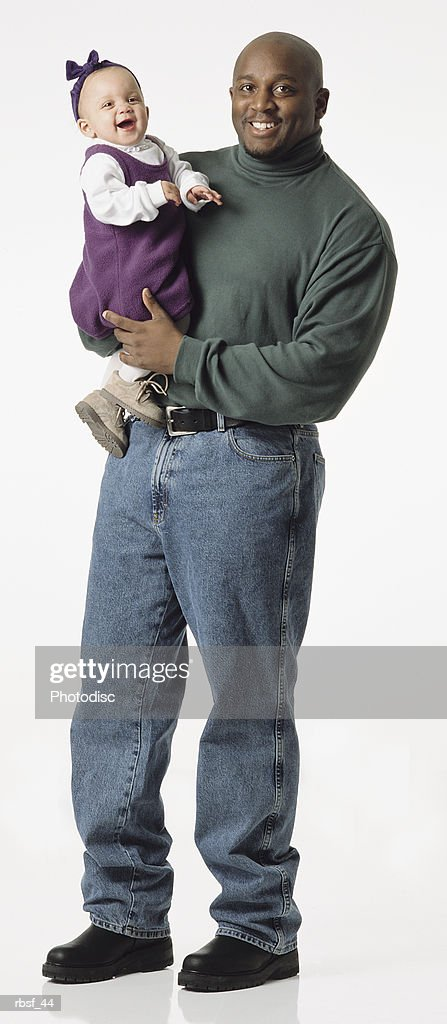 happy african american dad stands in green turtleneck and holds laughing little girl in purple with bow in head : Foto de stock