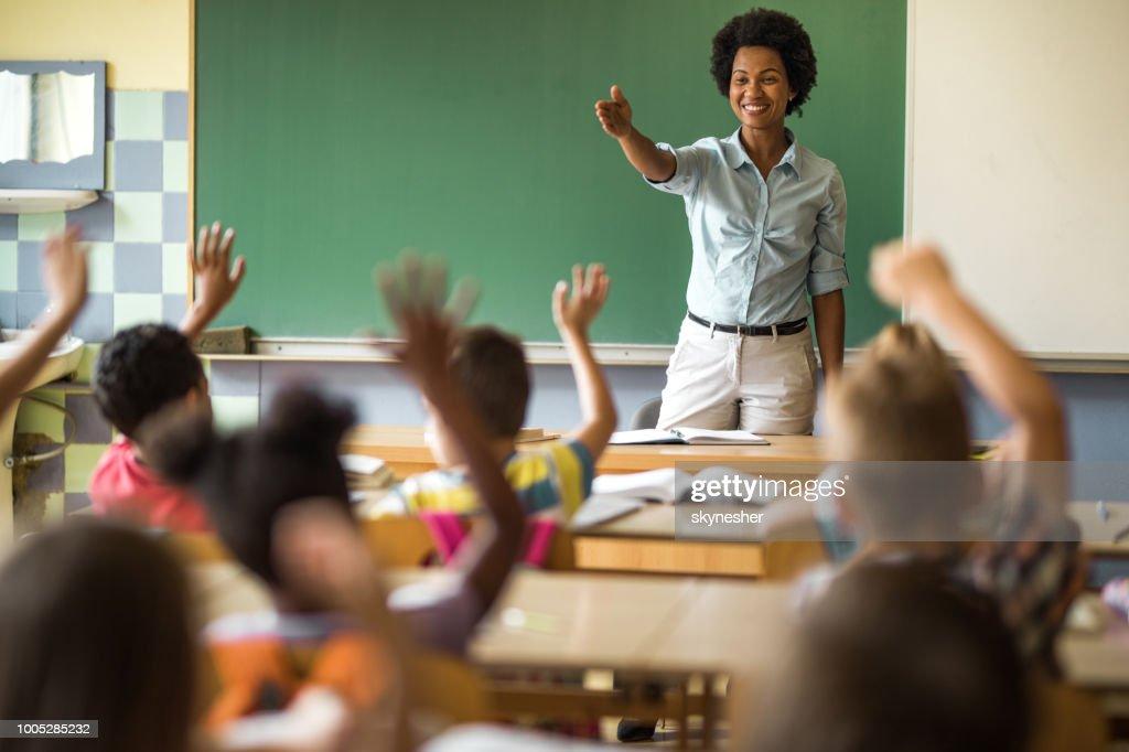 Afro-americano feliz professor elementar visando miúdo de escola, para responder sua pergunta. : Foto de stock