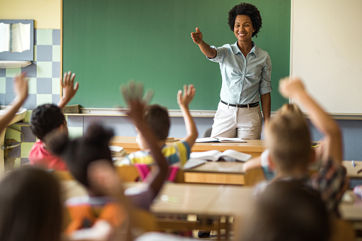 Happy African American elementary teacher aiming at school kid to answer her question. 1005285232