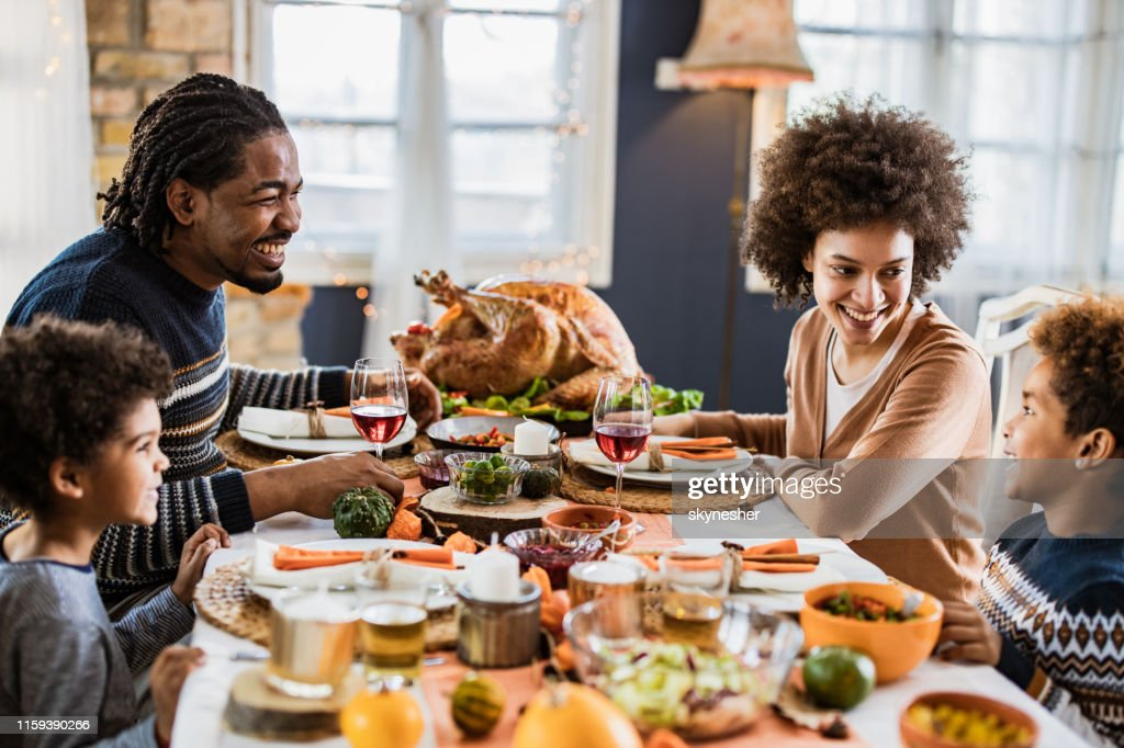 Happy African American family communicating while having Thanksgiving lunch in dining room. : Stock Photo