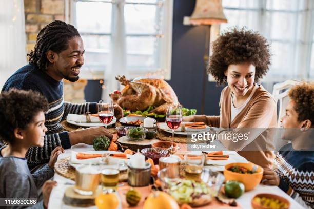 happy african american family communicating while having thanksgiving lunch in dining room. - thanksgiving holiday stock pictures, royalty-free photos & images
