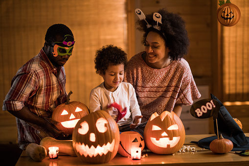 Happy African American family enjoying in Halloween at home. 1007047276