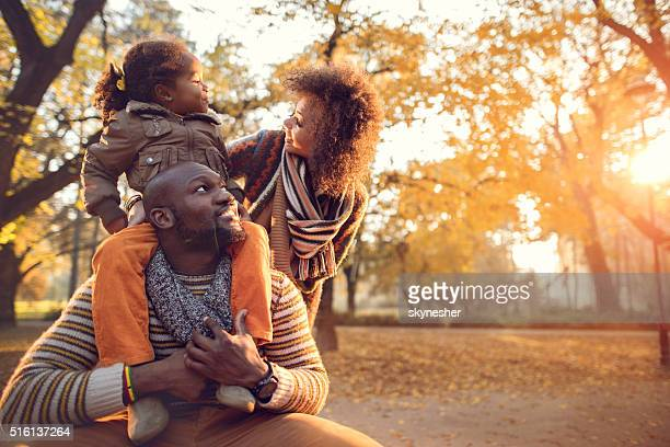 Happy African American family enjoying in nature during autumn.