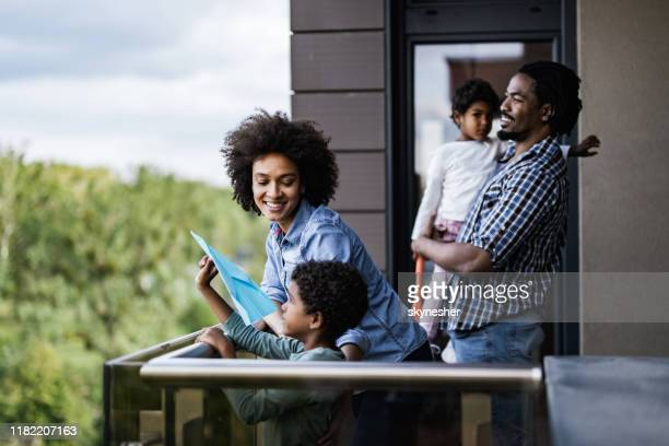 happy african american family enjoying on a balcony. - balcony stock pictures, royalty-free photos & images