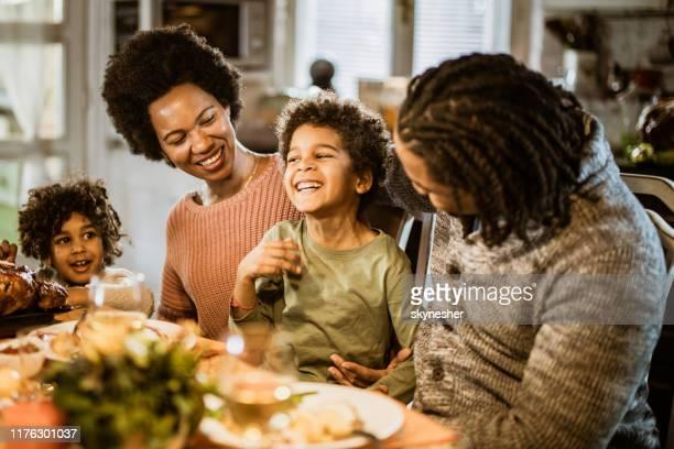 família feliz do americano africano que aprecia ao ter o almoço na sala de jantar. - african american family dinner - fotografias e filmes do acervo